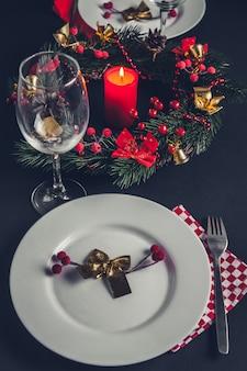 Schönes weihnachtsessengedeck für zwei. tisch mit kranz und kerze verziert.