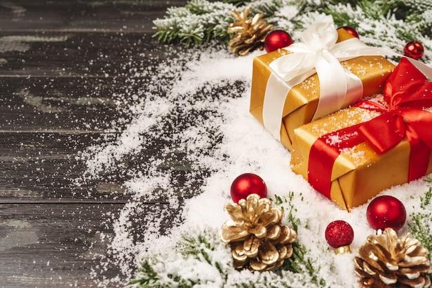 Schönes weihnachtsgeschenk mit schneebedeckten feiertagsdekorationen auf tabelle