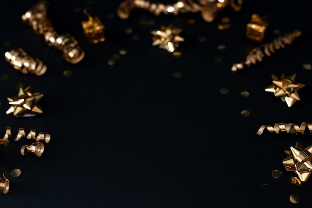 Schönes weihnachtsgoldener silberner deco flitter auf hintergrund des dunklen schwarzen.