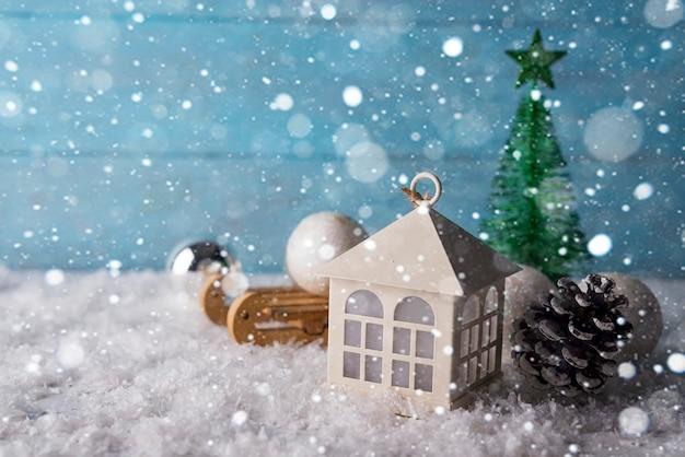 Schönes weihnachtshaus mit tanne drei auf hölzernem schneehintergrund