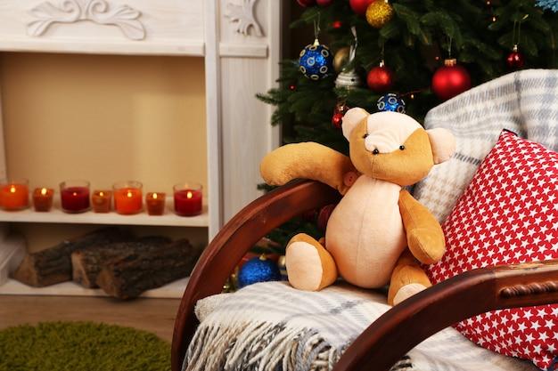 Schönes weihnachtsinterieur mit schaukelstuhl, dekorativem kamin und tannenbaum