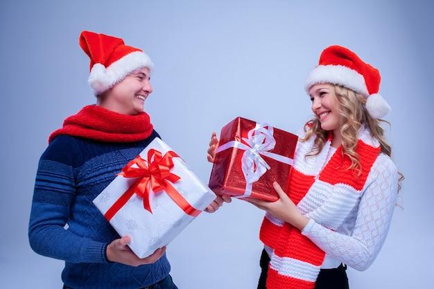 Schönes weihnachtspaar in weihnachtsmann-hüten mit geschenken auf blauem hintergrund