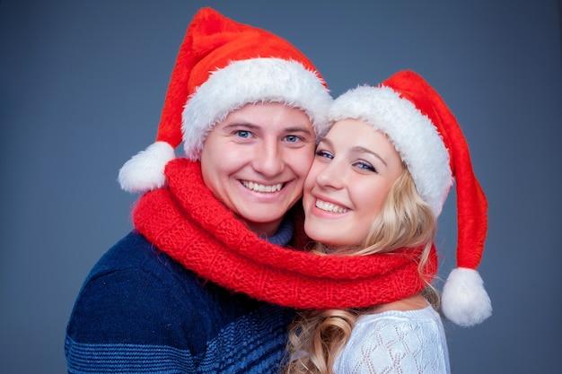 Schönes weihnachtspaar in weihnachtsmann-hüten posiert auf blau mit rotem schal