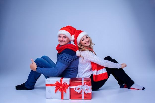 Schönes weihnachtspaar in weihnachtsmannmützen, das mit geschenken auf blau sitzt