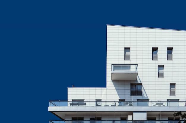 Schönes weißes holzgebäude unter dem klaren blauen himmel