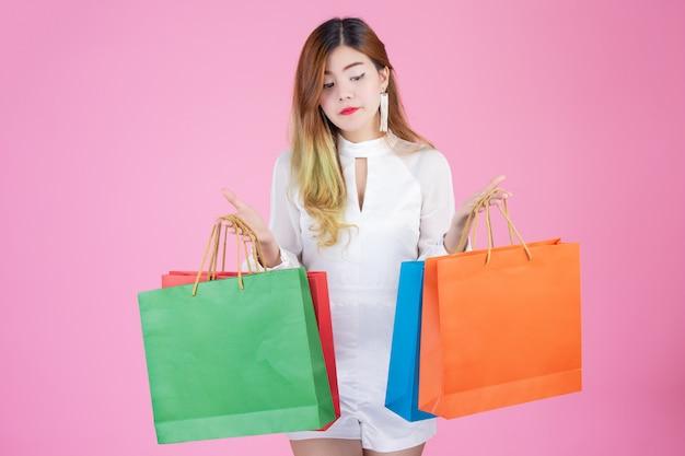 Schönes weißes mädchen, das eine einkaufstasche, eine mode und eine schönheit hält
