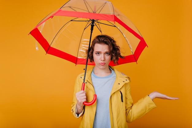 Schönes weißes mädchen, das traurige gefühle ausdrückt, während es unter regenschirm steht. innenfoto der schüchternen verärgerten dame trägt herbstkleidung, die sonnenschirm hält.