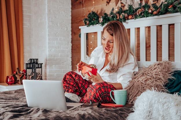 Schönes weißes mädchen im neujahrspyjama, das ein geschenk öffnet und per videoanruf spricht