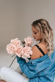 Schönes weißes mädchen mit blumen. atemberaubendes brünettes mädchen mit großen blumenstraußblumen der rosen. nahaufnahmegesicht der jungen schönen frau mit einer gesunden sauberen haut.