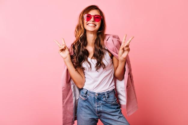 Schönes weißes mädchen mit dem langen gewellten haar, das mit aufregung aufwirft. innenporträt der optimistischen ingwerfrau, die auf rosa herumalbert.