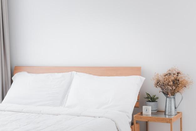 Schönes weißes sauberes gemütliches schlafzimmerinterieur mit grünem und getrocknetem blumentopf