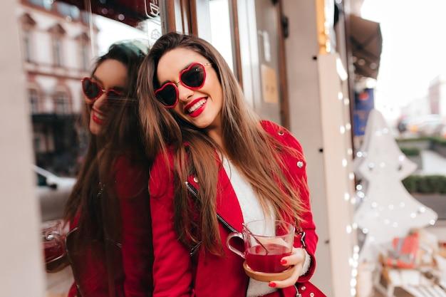 Schönes weißes weibliches modell trägt lustige sonnenbrille, die nahe restaurant lacht