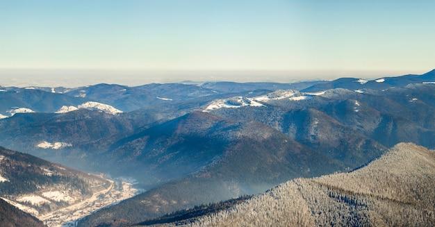 Schönes winterpanorama mit frischem schnee. gestalten sie mit gezierten kiefern, blauem himmel mit sonnenlicht und hohen karpatenbergen landschaftlich