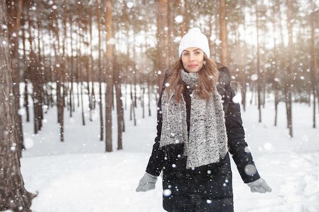 Schönes winterporträt der jungen frau in der schneebedeckten landschaft des winters