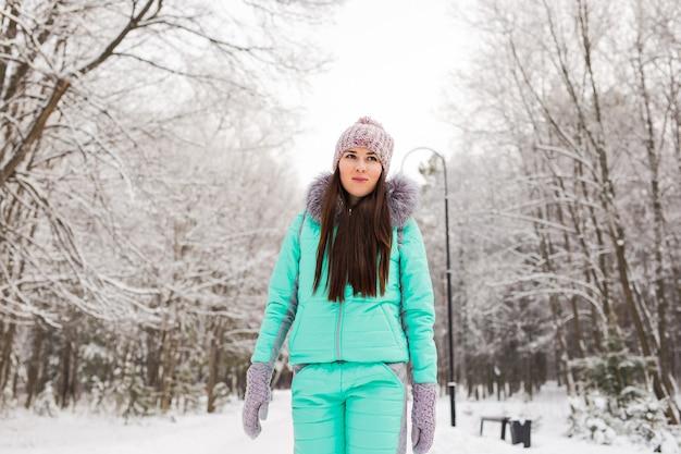 Schönes winterporträt der jungen frau in der verschneiten winterlandschaft