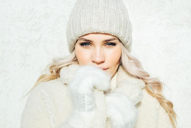 Schönes winterporträt von jungen blondinen die kamera auf weißem wandhintergrund betrachtend.