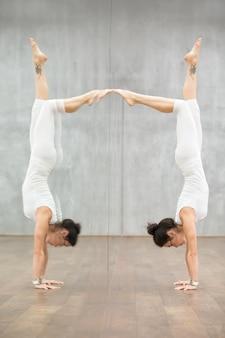 Schönes yoga: frau, die handstandhaltung tut