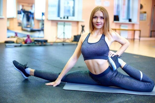Schönes yogatraining der jungen frau in der turnhalle