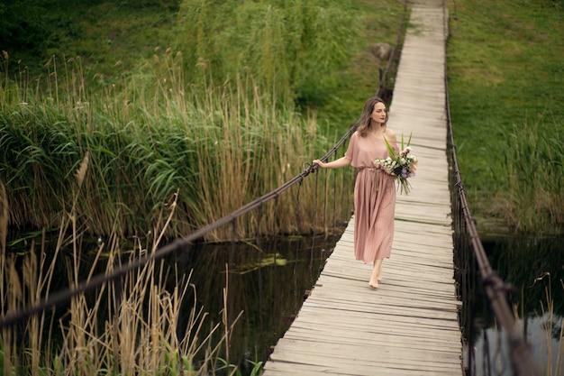 Schönes zartes mädchen in einem pfirsichfarbenen kleid gehend auf eine ländliche holzbrücke mit einem blumenstrauß von blumen