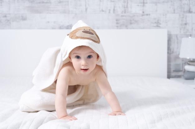 Schönes zehnmonatiges baby, das drinnen im hellen, modernen interieur mit handtuch nach dem bad auf dem bett sitzt. konzept für die babypflege.
