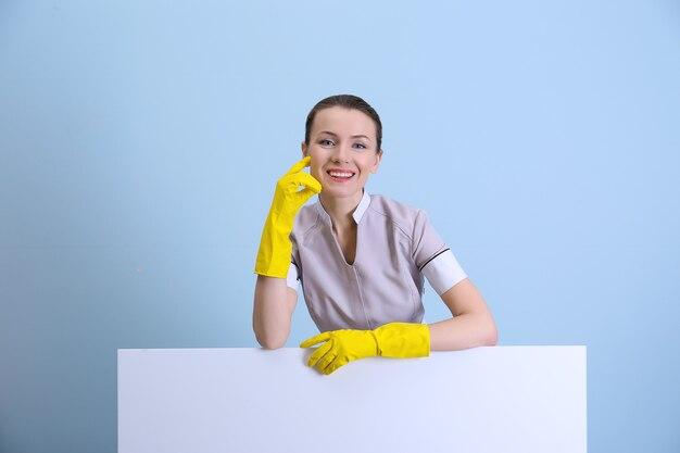 Schönes zimmermädchen in uniform auf farbigem hintergrund