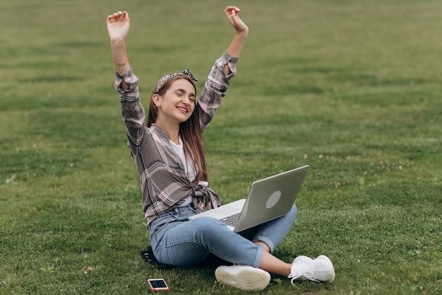 Schönes zufälliges weibliches sitzen auf gras unter verwendung des laptops. porträt der attraktiven jungen frau, die auf grünem gras im park sitzt