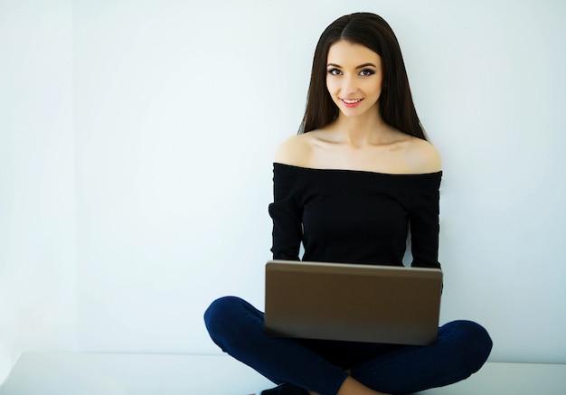 Schönheit arbeitet im hellen büro beim halten des computers in den händen