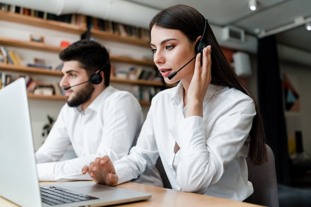 Schönheit arbeitet in call-center mit dem kopfhörer, der kundenanrufe beantwortet