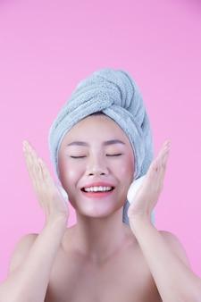 Schönheit asien wäscht ihr gesicht auf rosa hintergrund.