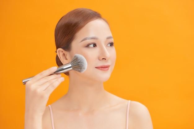 Schönheit. bilden. schöne frau, die trockene kosmetische tongrundierung auf dem gesicht unter verwendung von make-up-pinsel anwendet.