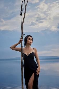 Schönheit brünette frau in einem schwarzen kleid wirft in einem see vor einem blauen himmelshintergrund auf. sexy frau des langen haares und schönes schönheitsmake-up auf ihrem gesicht