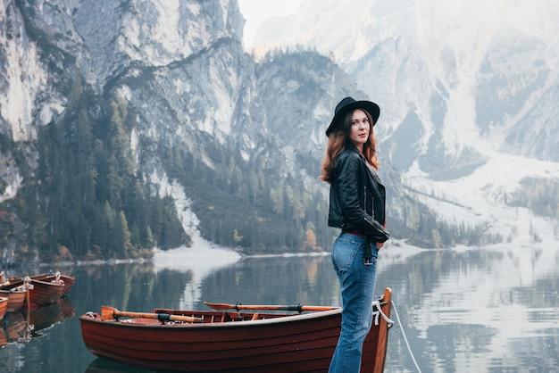 Schönheit der natur und mädchen auf einem bild. frau im schwarzen hut, der majestätische berglandschaft nahe dem see mit booten genießt