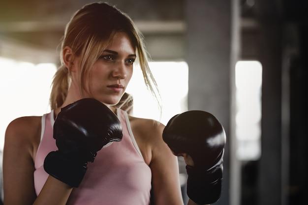 Schönheit des sportlichen mädchens des porträts mit den hinteren boxhandschuhen ausbildend an der turnhalle