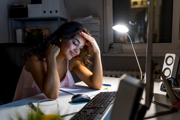 Schönheit, die als innenarchitekt arbeitet, spät in der nacht im büro mit dem zeichnen bleibend