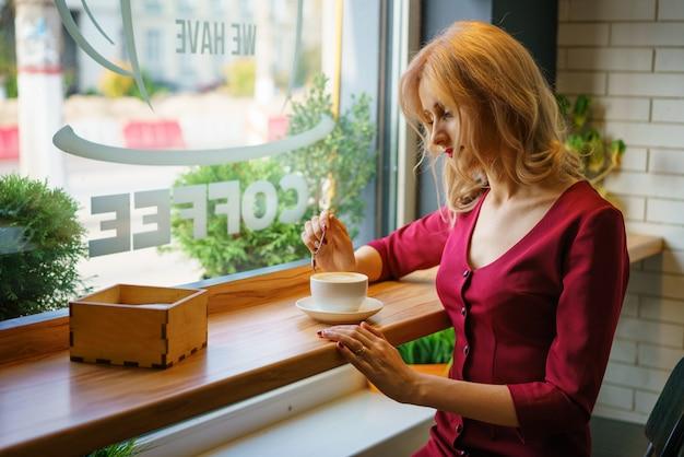 Schönheit, die am fenster in einem trinkenden kaffee des cafés sitzt.