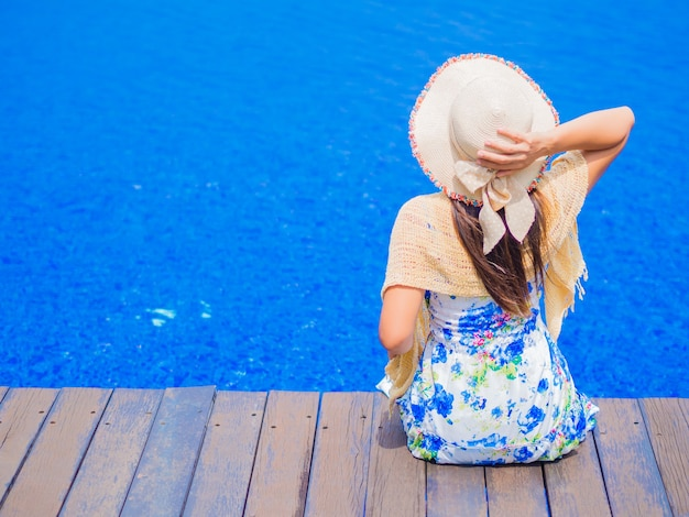 Schönheit, die am rand des swimmingpools sitzt