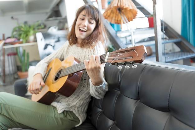 Schönheit, die auf einem sofa sitzt und gitarre spielt