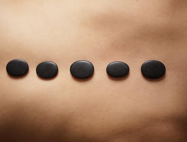 Schönheit, die badekurort-heiße stein-massage im badekurortsalon erhält.