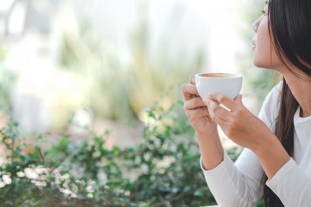 Schönheit, die ein langärmliges weißes hemd sitzt an einer kaffeestube trägt