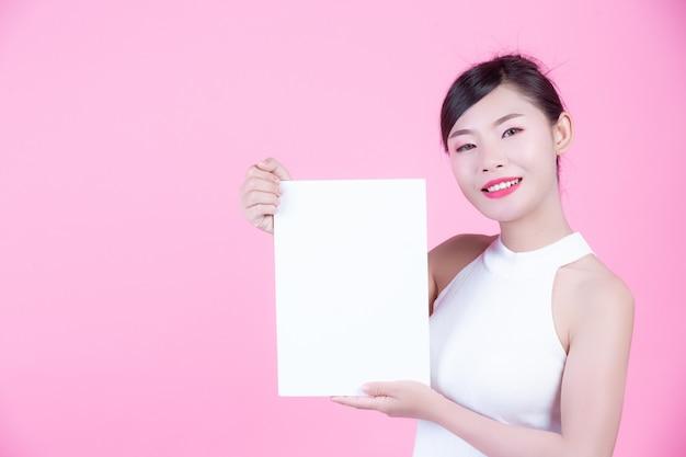 Schönheit, die ein weißes brettblatt auf einem rosa hintergrund hält.