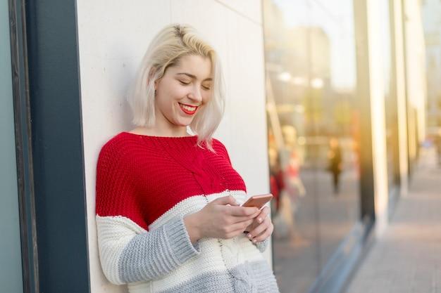 Schönheit, die eine mitteilung an ihrem telefon beim handeln schreibt.