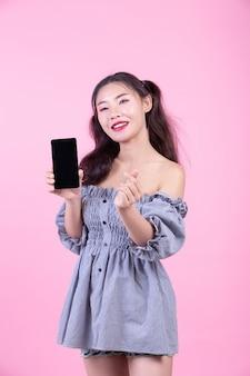 Schönheit, die einen smartphone auf einem rosa hintergrund hält.