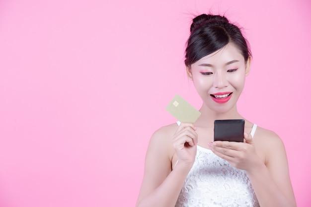 Schönheit, die einen smartphone und eine karte auf einem rosa hintergrund hält