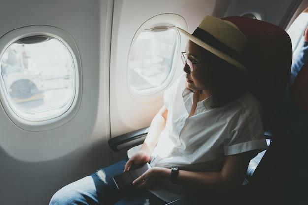 Schönheit, die einen strohhut unter verwendung eines intelligenten telefons beim im flugzeug sitzen trägt