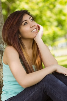 Schönheit, die gegen baum im park sitzt