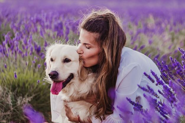 Schönheit, die ihren hund des goldenen apportierhunds auf den lavendelgebieten bei sonnenuntergang küsst.