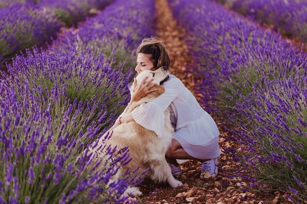 Schönheit, die ihren hund des goldenen apportierhunds auf den lavendelgebieten bei sonnenuntergang umarmt.