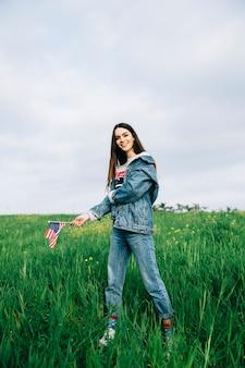 Schönheit, die in der zufälligen kleidung auf gras mit kleiner flagge bleibt