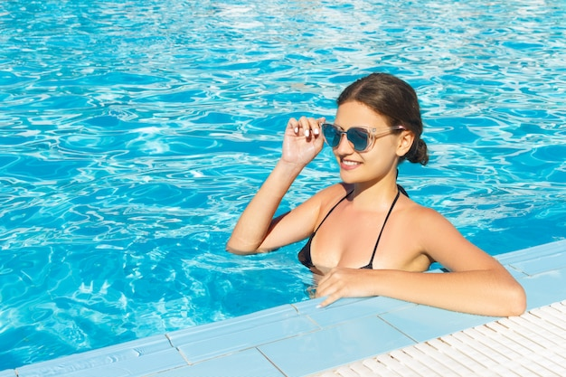 Schönheit, die in swimmingpool wasser in der sonnenbrille sich entspannt.