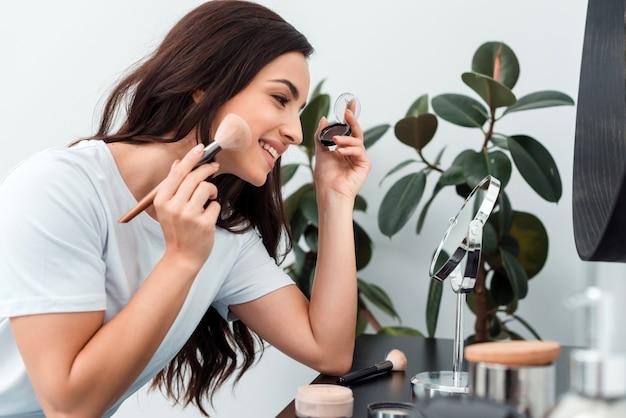 Schönheit, die make-up tut und make-upbürste und -lidschatten hält